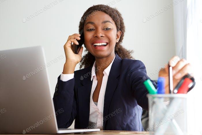 glückliche afrikanische Geschäftsfrau im Gespräch auf Handy im Büro