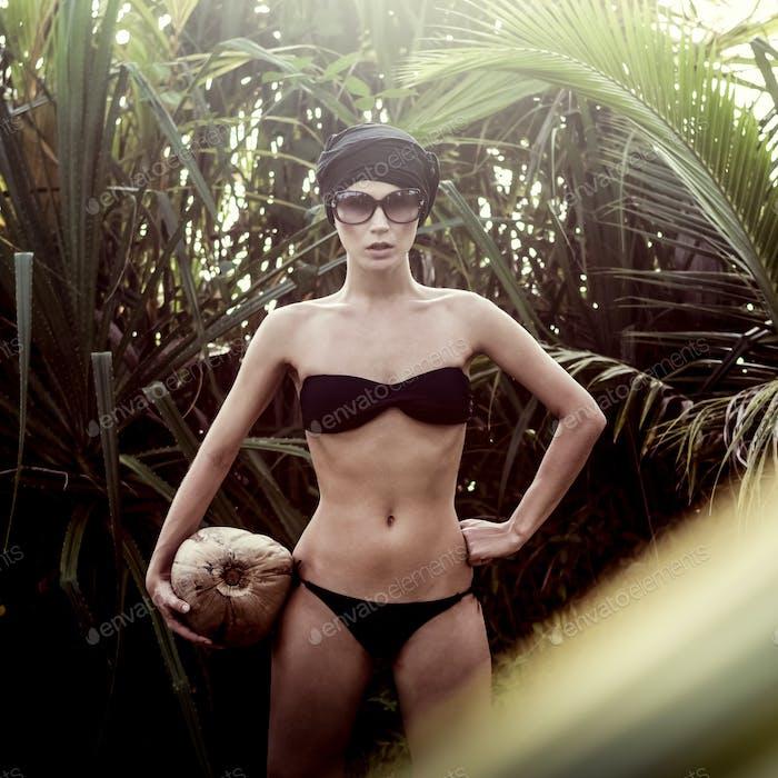 Mädchen in einem tropischen Dschungel mit Kokosnuss