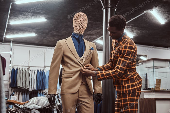 Афро-американский мужчина, одетый в модный элегантный костюм, работает в магазине классической мужской одежды.