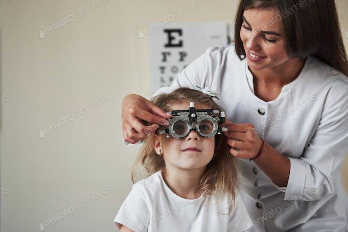 Fröhliche Atmosphäre. Arzt überprüft kleines Mädchen Anblick und stimmt den Phoropter