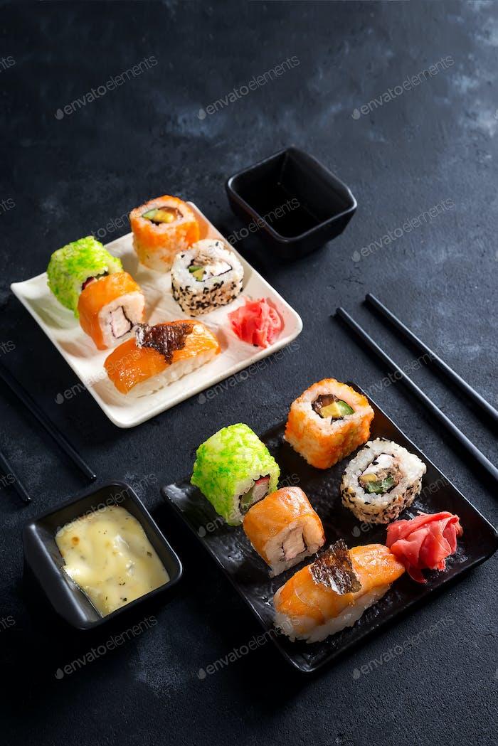Traditionelles japanisches Essen - Sushi, Brötchen, Essstäbchen, Sojasauce auf schwarzem Schiefergrund. Sushi-Menü