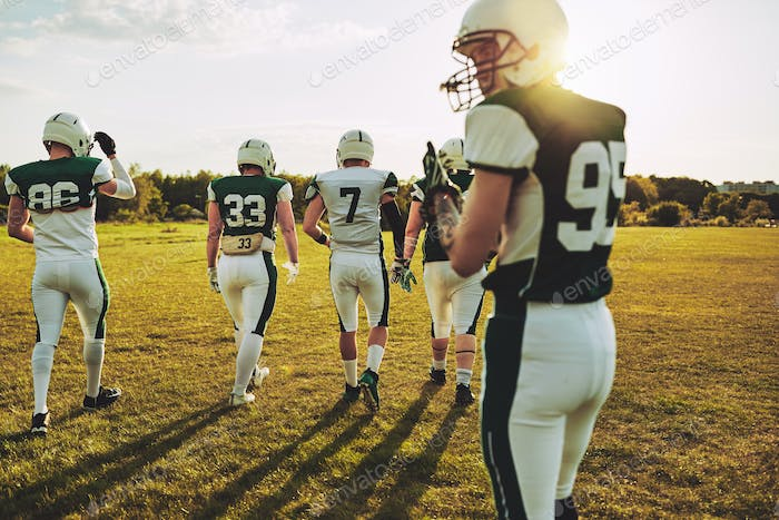 Group of American football players walking together on a field