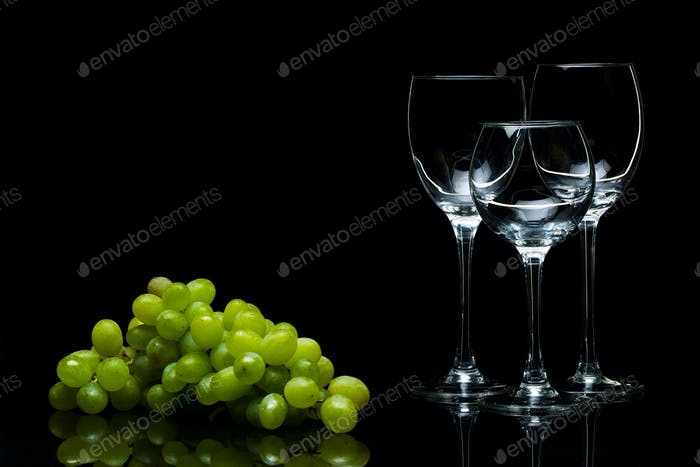Glasses for wine and a bunch of grapes on a black background