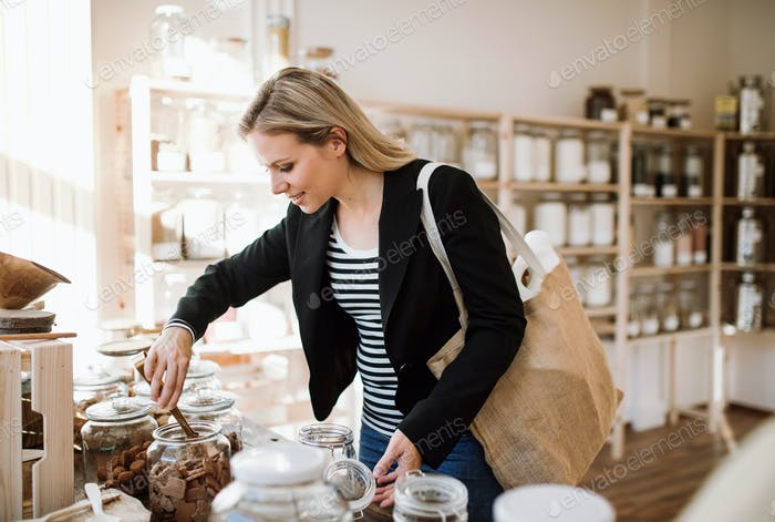 A young happy woman buying groceries in zero waste shop.