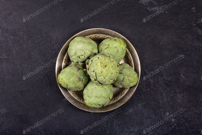 Pile of green Spanish or Italian Artichokes on the metal rustic plate