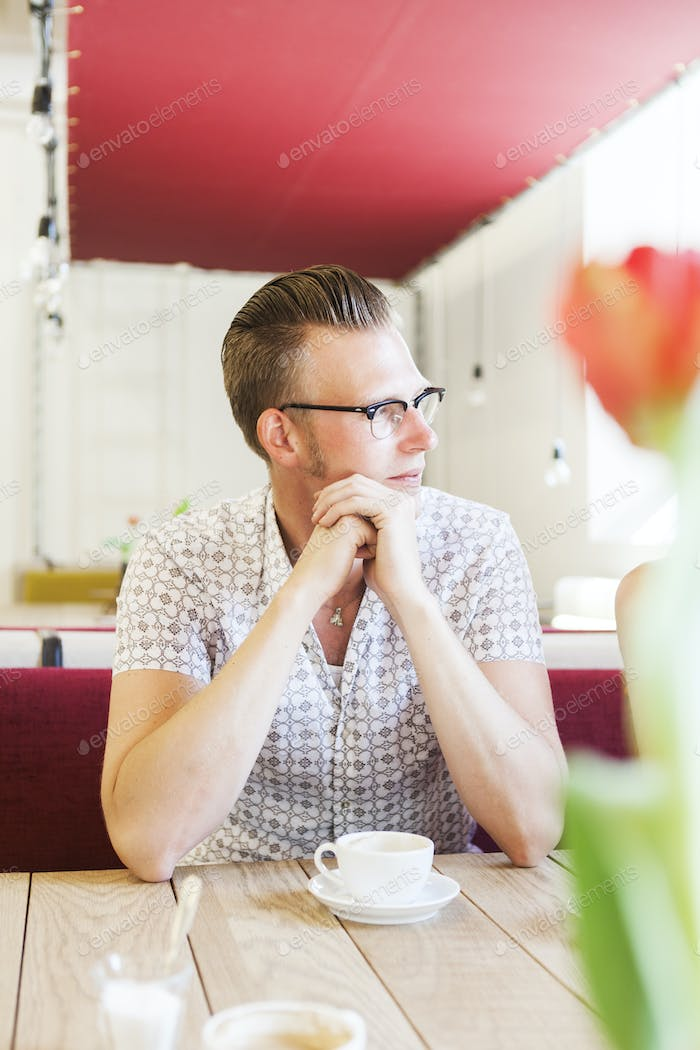 Young man looking away while sitting at cafe table