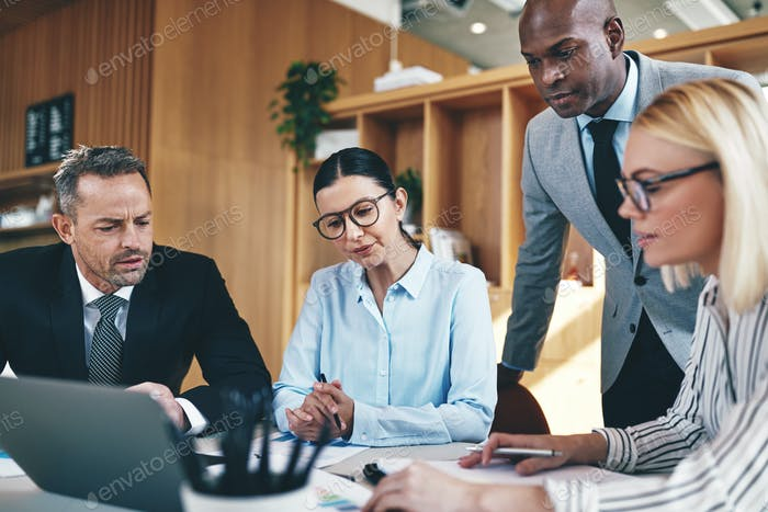 Diverse businesspeople going over paperwork together during an office meeeting