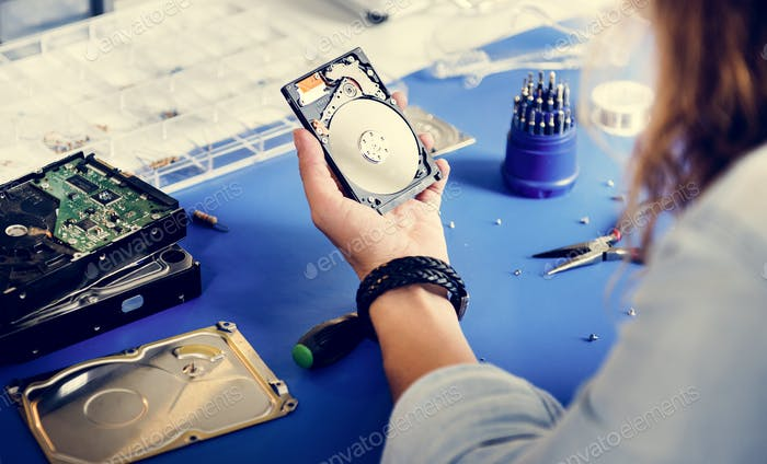 Technician holding HDD fixing at electronic repair shop