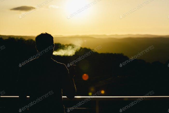 Man smoking watching the sun set