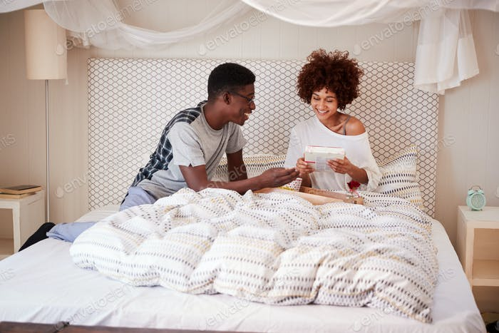 Millennial African American man giving his partner breakfast and gifts in bed to celebrate