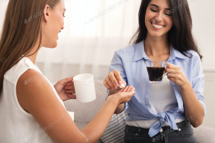 Two Girls Adding Sugar Drinking Coffee Sitting On Couch Indoor