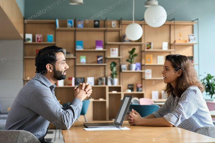 Indian hr employer listening latin candidate at job interview meeting.