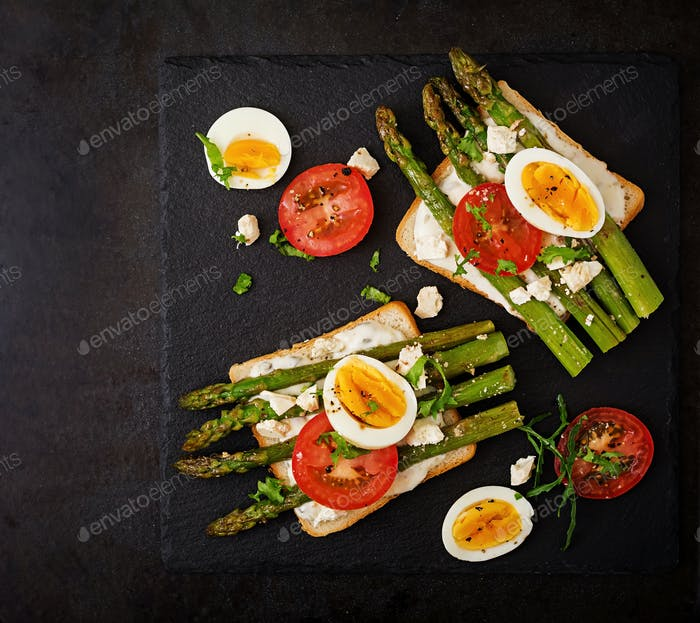 Sandwiches with caramelized asparagus, feta cheese, tomatoes and eggs. Top view