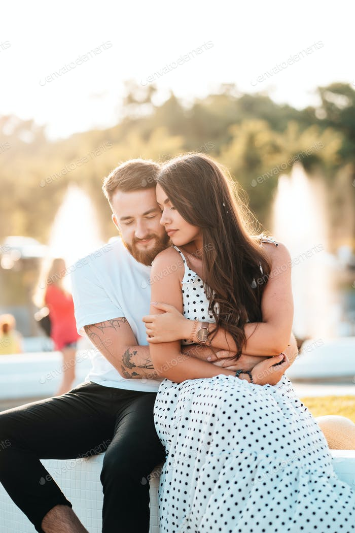 Handsome guy hugs a beautiful girl on a background of a fountain