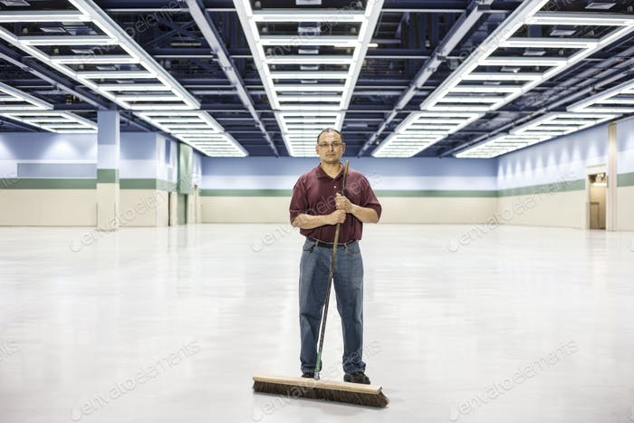 An hispanic man standing with a broom in a large convention cener space.