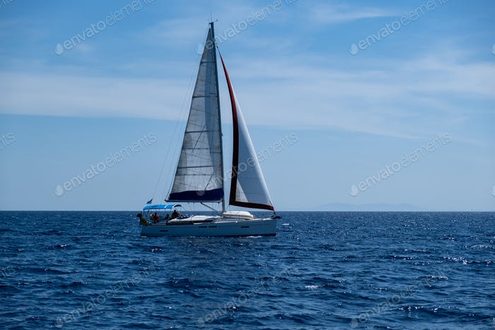 Sailing boat with open white sails, blue sky and rippled sea background