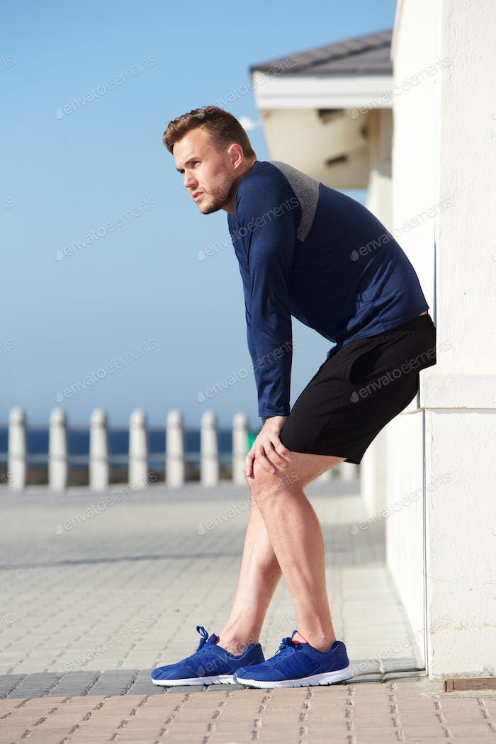 active young man resting outside after workout