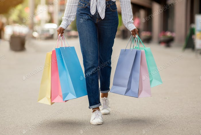 Shopping with bonuses and gifts. African american woman with many bags walks at street