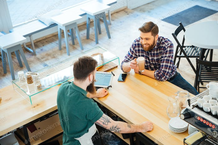 Cheeful man drinking coffee in cafeteria and talking to barista