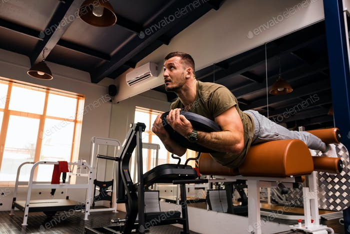 Young sportive man does hyperextension exercise in gym