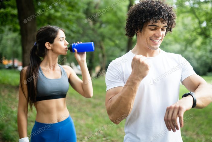 Couple drinks water after jogging to replenish energy and to hydrate