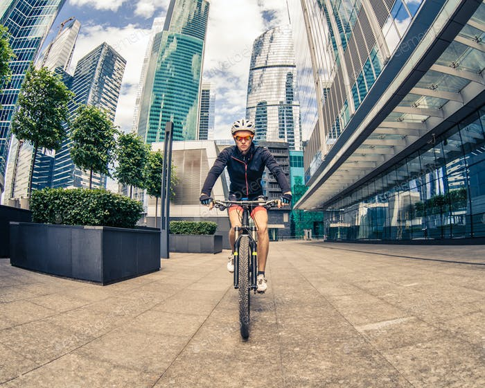 sportsman cyclist rides on bicycle at street among skyscrapers
