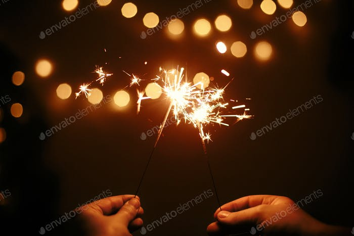 Glühende Wunderkerzen in Paarhänden auf dem Hintergrund der goldenen Weihnachtsbaum-Lichter