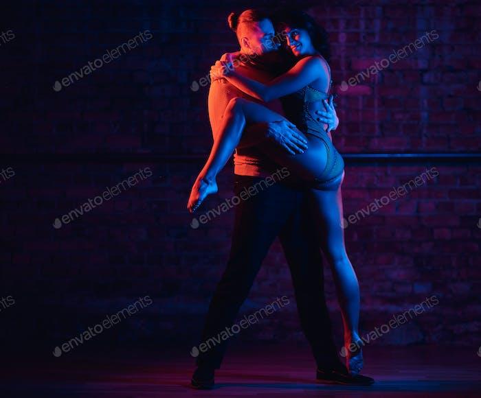 Schönes Paar tanzen in einem Nachtclub. Tänzer, die im Dunkeln mit Beleuchtung  auftreten