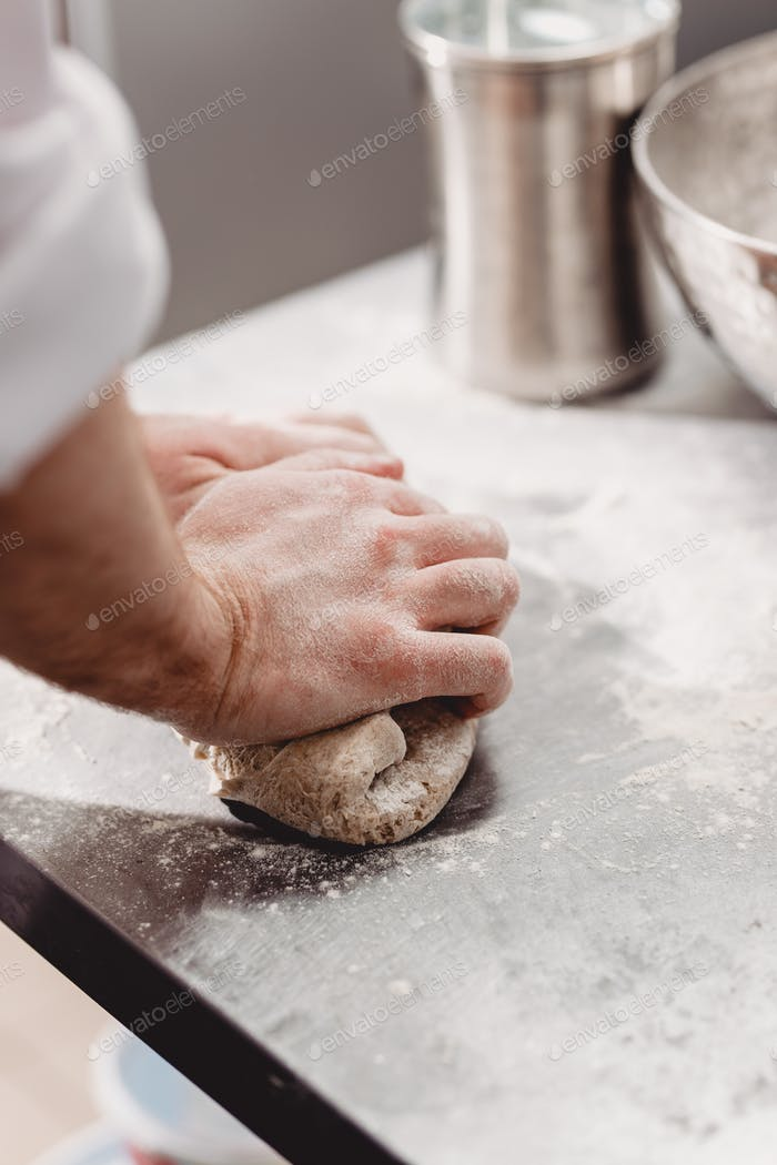 Baker punchs down the dough in the kitchen in the bakery