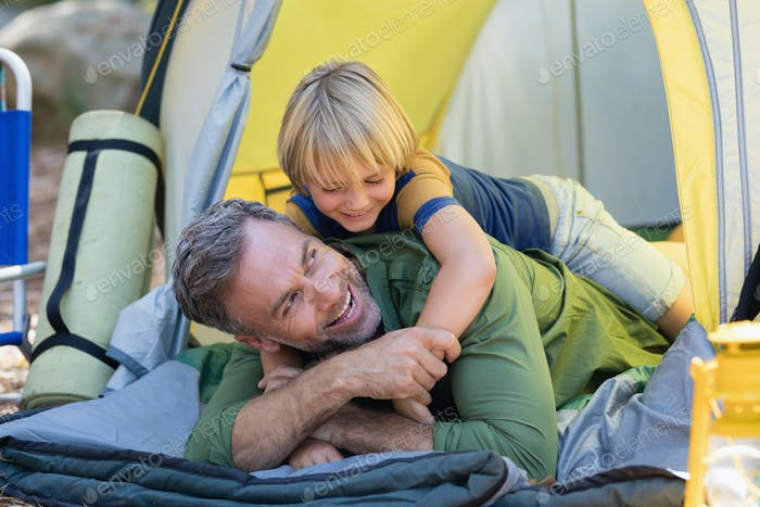Playful little boy lying on father in tent
