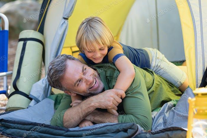 Verspielter kleiner Junge liegend auf Vater im Zelt