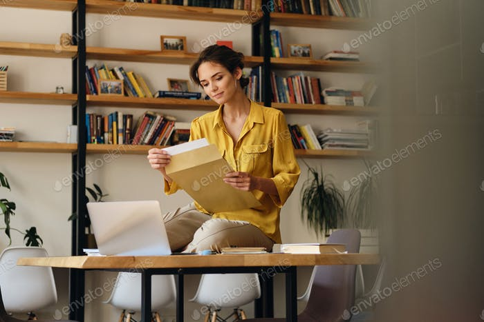 Pretty smiling woman in yellow shirt sitting on desk with papers dreamily working in office