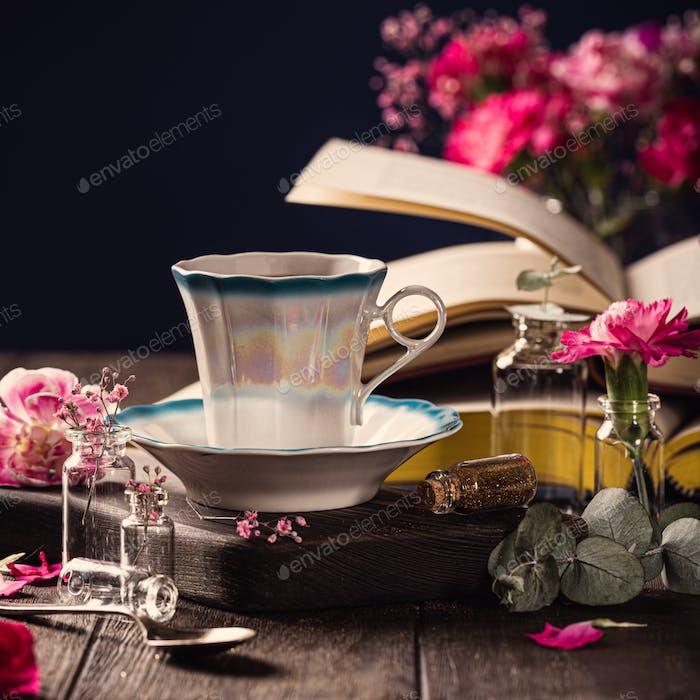 Tasse Kaffee, alte Bücher und rosa Nelken Blumen