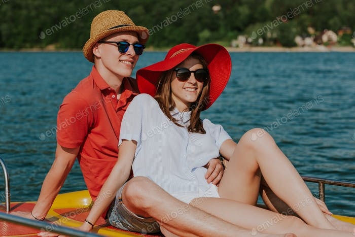 Portrait of smiling couple in love enjoying boating on the lake.