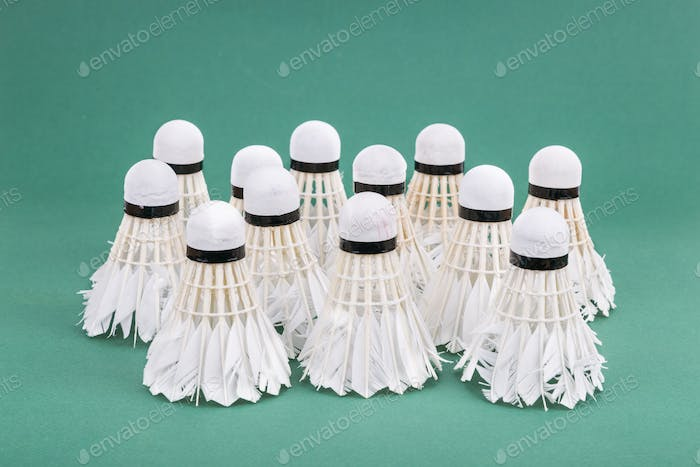 Group of used and worned out badminton shuttlecock on green cour