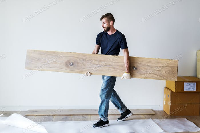 Carpenter man installing wooden floor