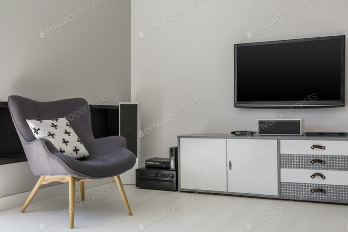 Television above cabinet next to grey armchair with patterned pi