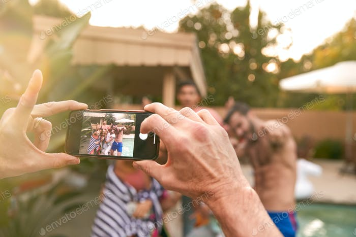 Group Of Friends Outdoors Relaxing By Swimming Pool Posing For Photo On Mobile Phone