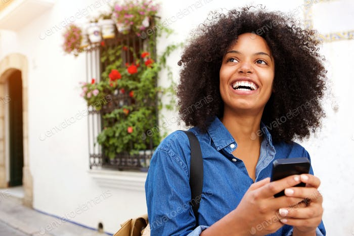 Close up smiling woman with mobile phone walking on street