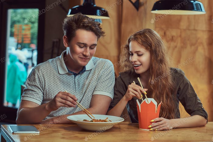 Jóvenes estudiantes de pareja sentados en la mesa en la cantina de la universidad durante un descanso.