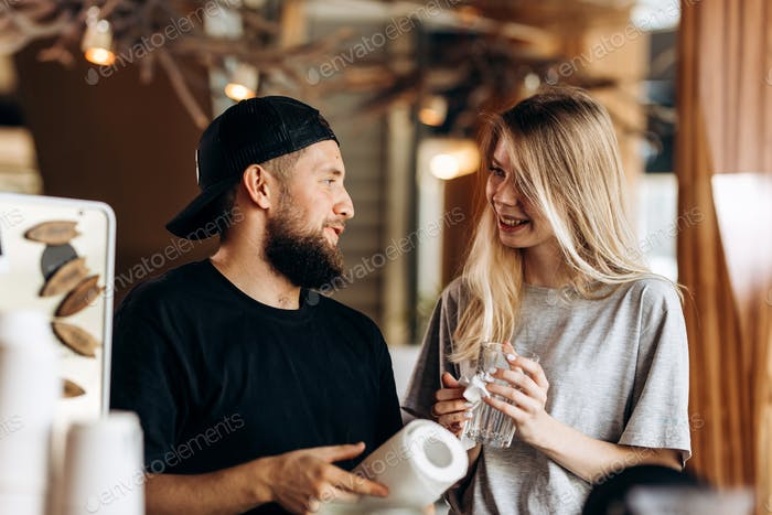 Two young smiling people,a blonde girl and man with beard.dressed in casual outfit, stand next to