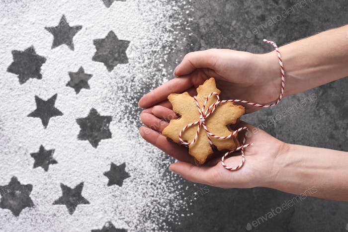 Close up of woman's hands holding gingerbread cookies