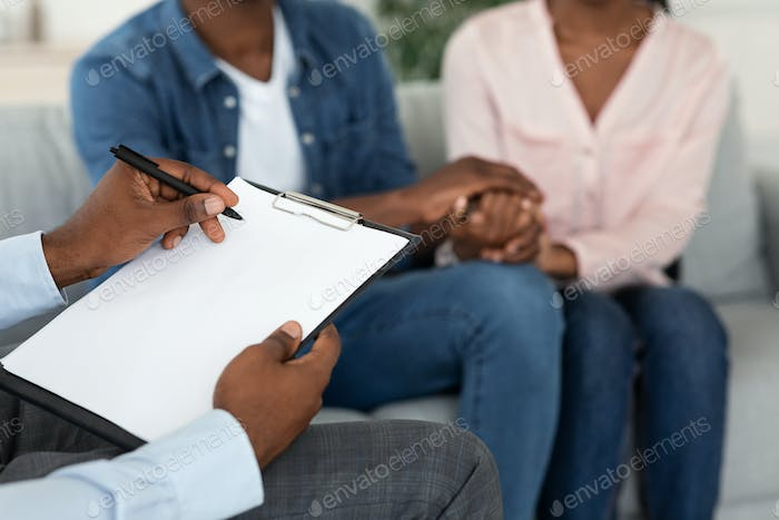 Marital Counselor Taking Notes At Therapy Session With African American Spouses