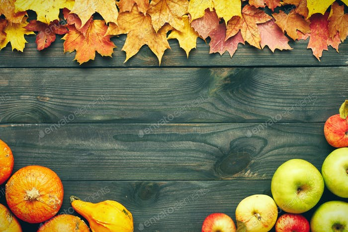 Herbstblätter, Äpfel und Kürbisse über Holzhintergrund