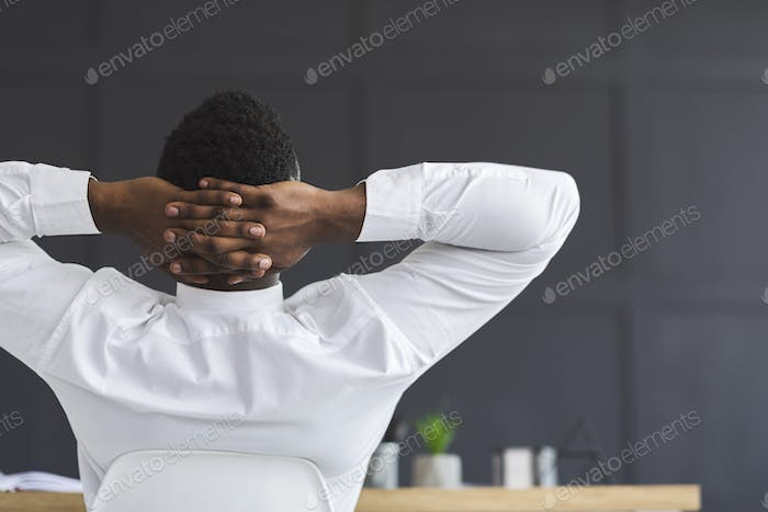 Back view of black employee relaxing in office