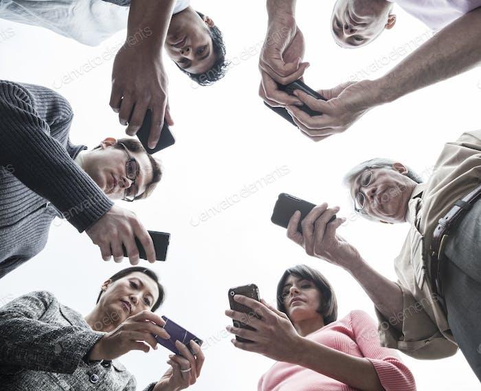 Blick auf ein gemischtes Team von Menschen, die ihre Handys betrachten.