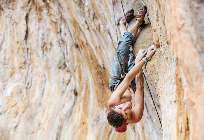 Männlicher Kletterer auf einer Klippe, Blick von oben