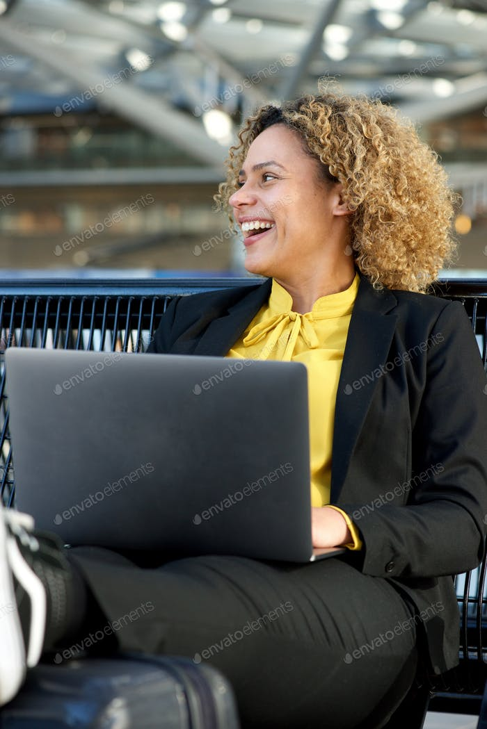 happy businesswoman sitting with laptop computer
