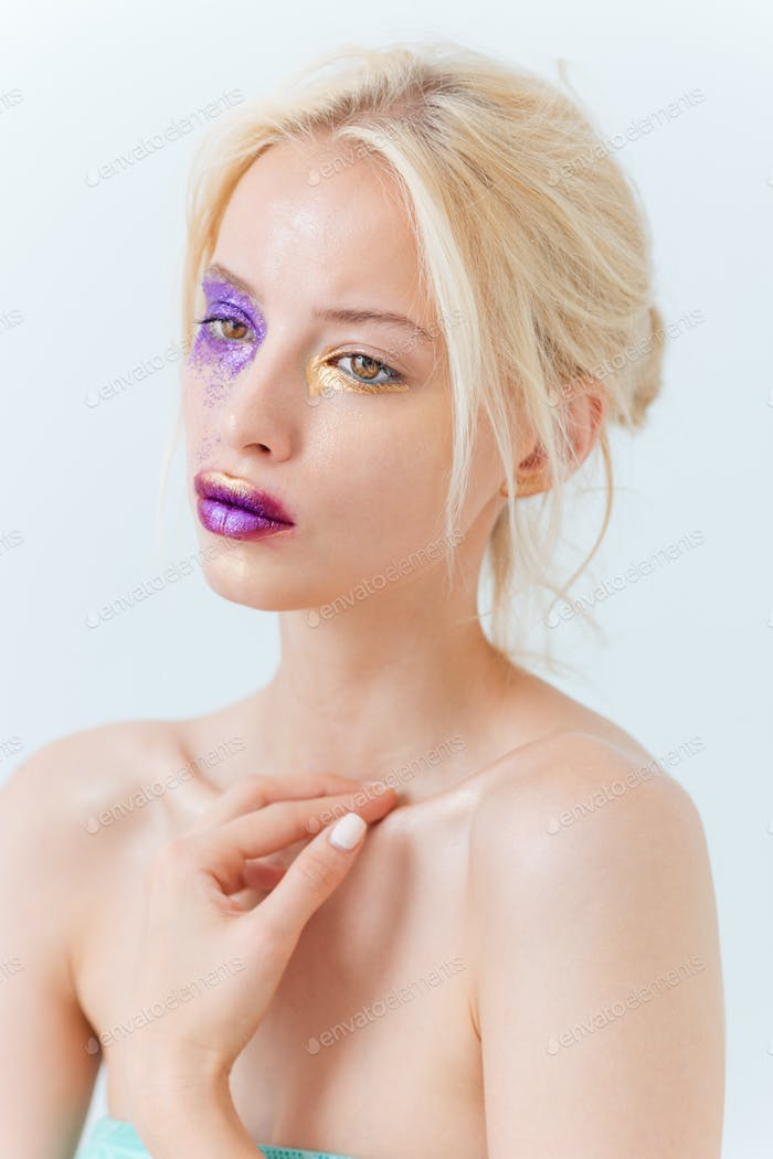 Portrait of beautiful young woman with purple creative makeup