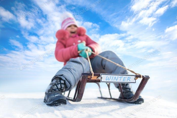Happy Girl Rodeln im Freien an klaren Wintertag